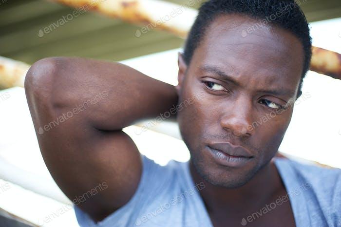 Atractivo negro Hombre con la Mano detrás de la cabeza mirando Lejos
