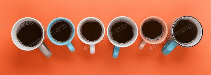 Kaffee in den verschiedenen Tassen auf dem leuchtend orangefarbenen Hintergrund. Flatlay, fröhliches Tageskonzept