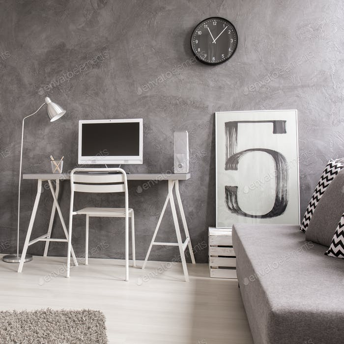 Grey office with computer and sofa