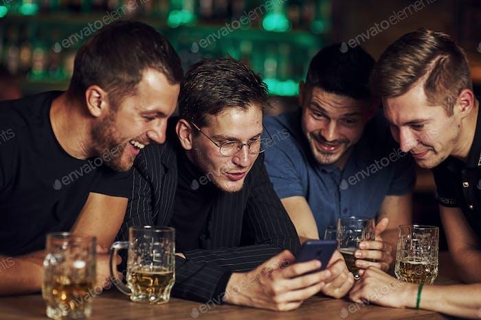 Drei Freunde ruhen in der Kneipe mit Bier in der Hand. Konversation haben