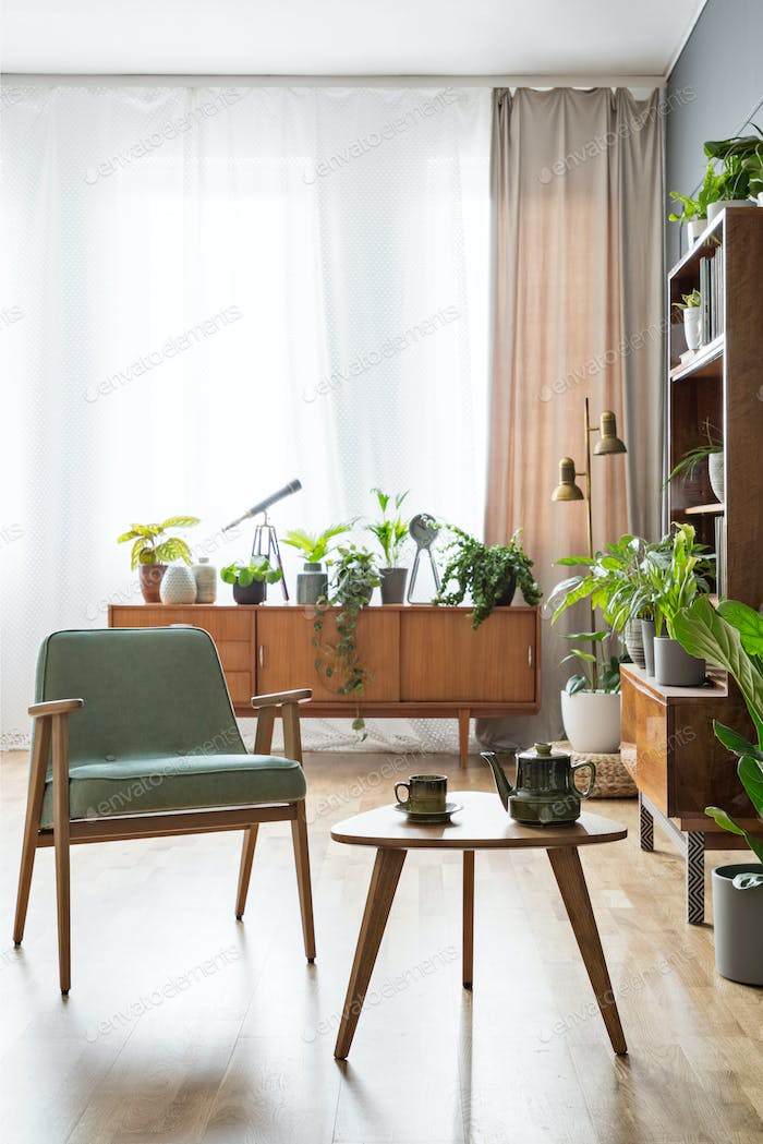 Real photo of a chair standing next to a small table with pot on