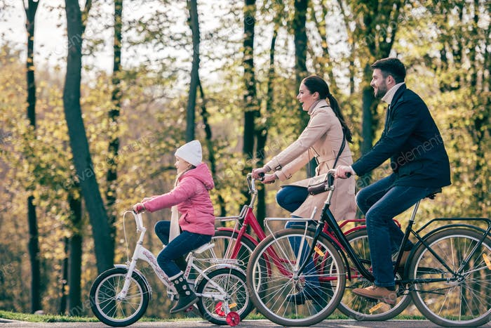 Side view of happy family riding bikes in autumn park