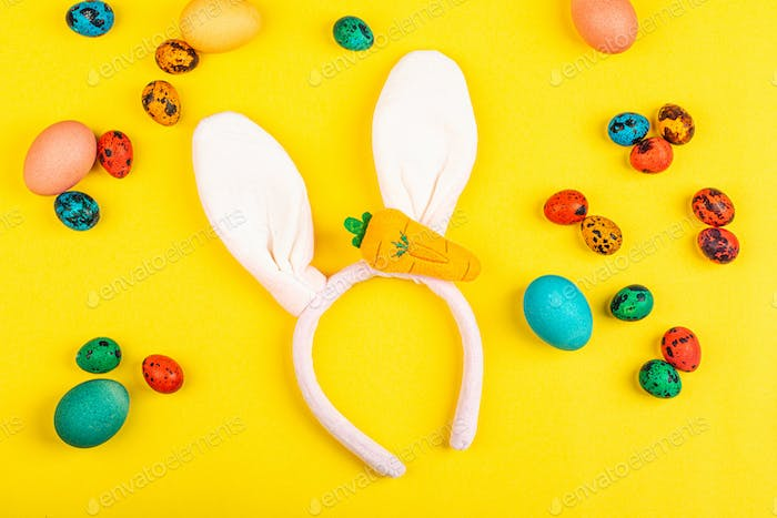 Flat Lay of Colored Easter Eggs And Bunny Ears on Yellow Background