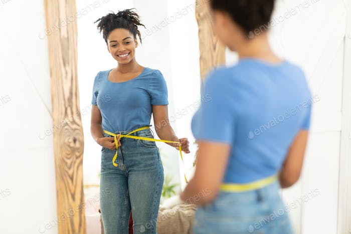 Happy Black Girl After Weight Loss Measuring Waist At Home