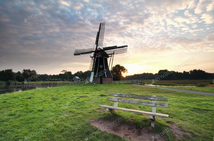wooden bench near windmill at sunrise