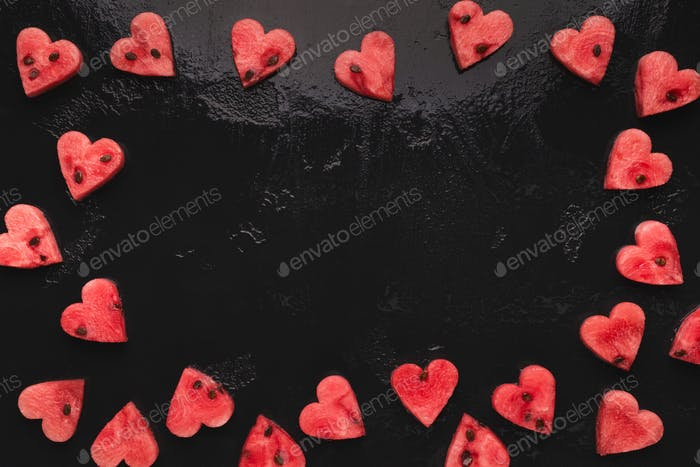 Watermelon hearts frame on black background, empty space