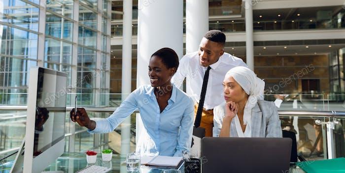 Männliche und weibliche Führungskräfte diskutieren über Computer am Schreibtisch