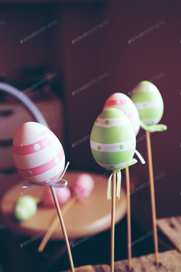 A beautiful close-up of 3 easter eggs on sticks over tables with