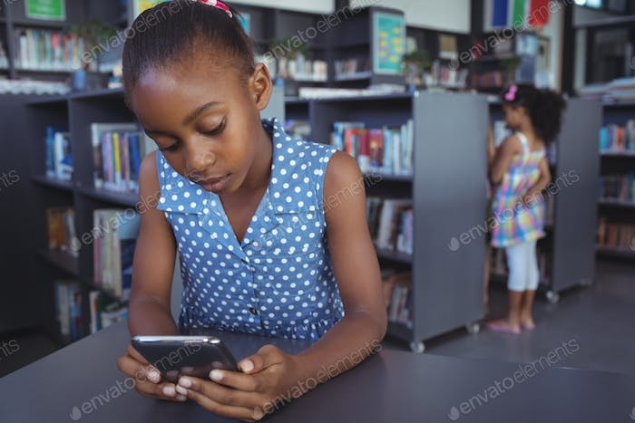 Girl using mobile phone at desk in library