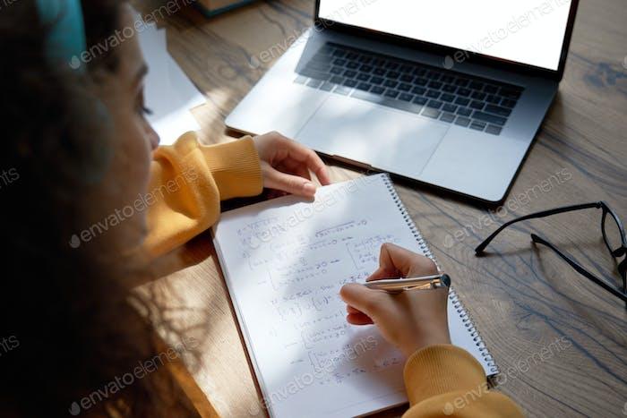 Niña adolescente estudiante escribiendo ecuaciones aprender matemáticas en línea, vista sobre el hombro.