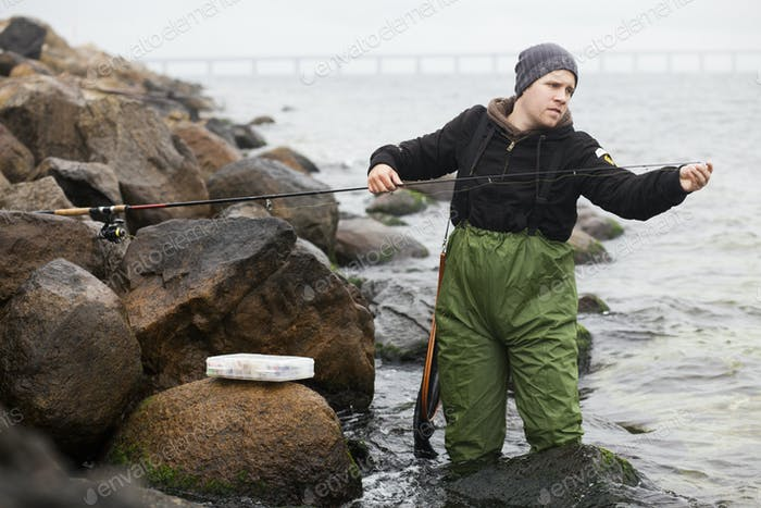 Man repairing fishing rod while standing in lake by rocks