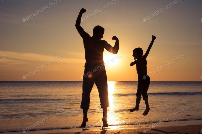 Vater und Sohn spielen am Strand bei Sonnenuntergang Zeit.