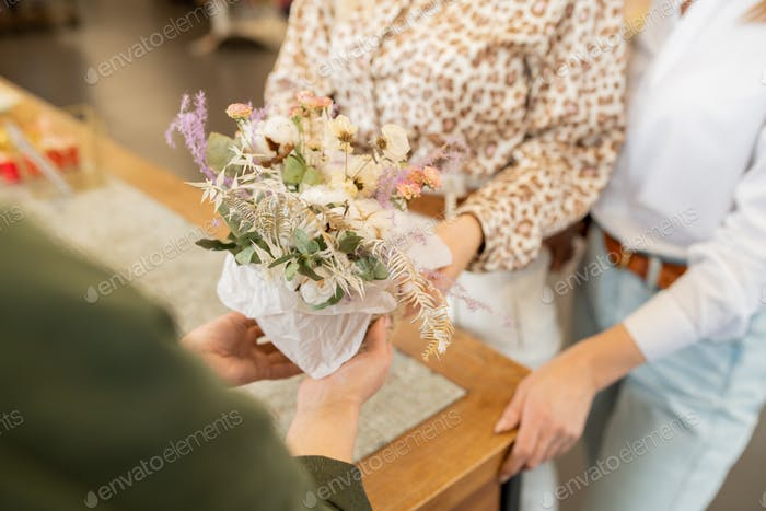 Hands of young owner of florist shop holding bunch of flowers over counter