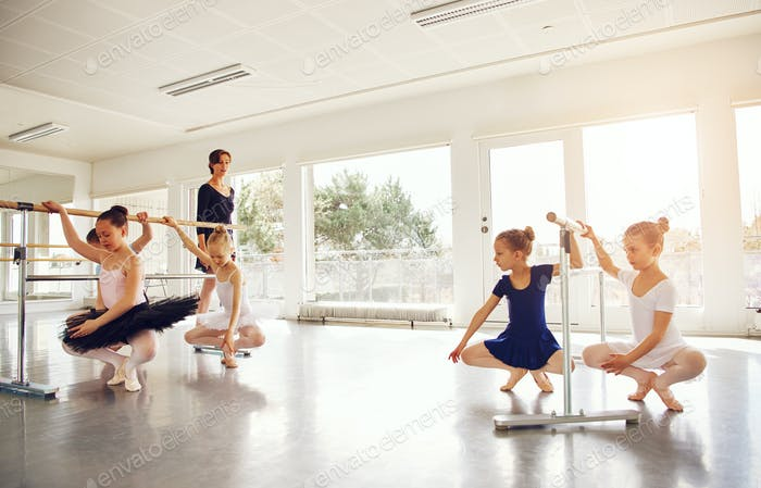 Teacher watching little girls practicing ballet