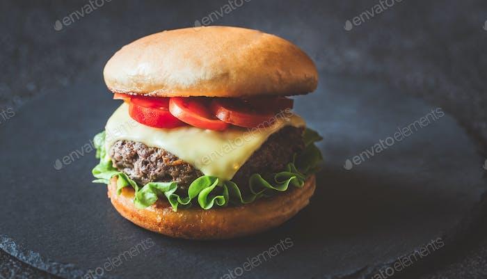 Hamburger auf dem schwarzen Steinbrett
