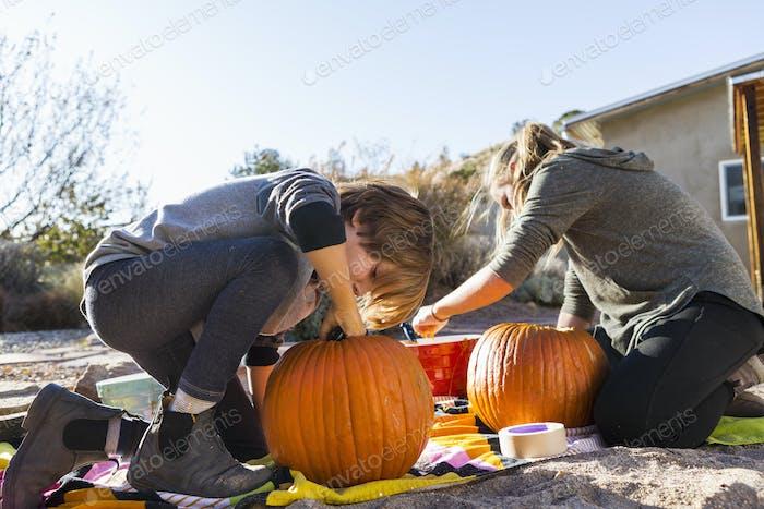 Ein Mädchen im Teenageralter und ihr Bruder schnitzen Kürbisse an Halloween.