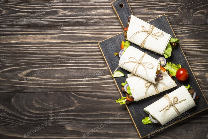 Burritos tortilla wraps with beef and vegetables on wooden backg
