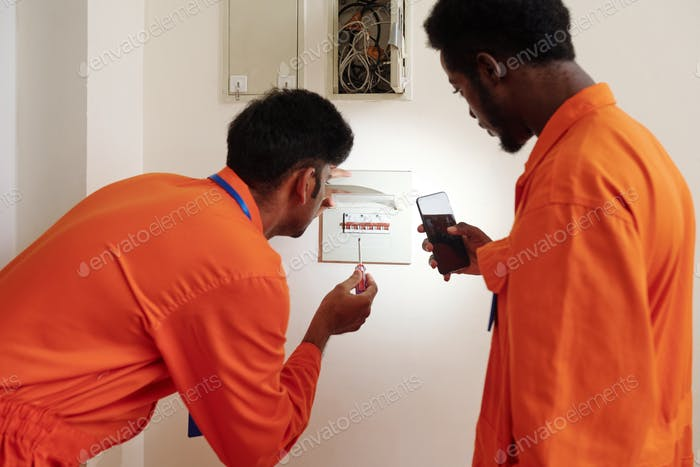 Electricians checking fuse box