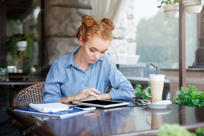 Young redhead girl using the tablet
