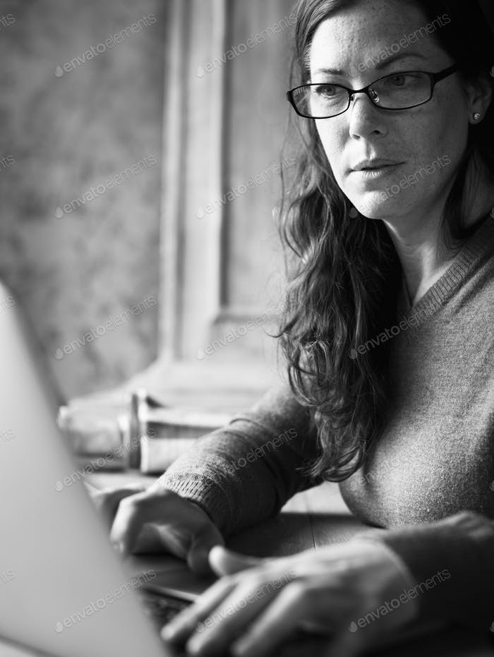 Caucasian woman using computer laptop grayscale