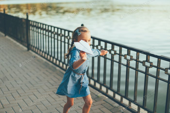 Girl running with toy paper airplane