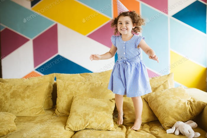 Pretty joyful little girl with dark curly hair in dress and birt