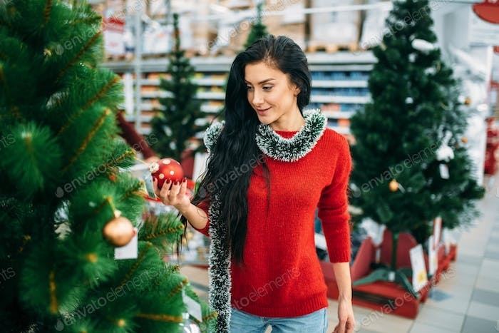 Woman looks on christmas tree toy in supermarket