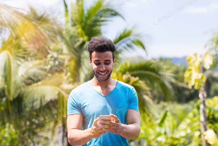 Happy Latin Man Using Cell Smart Phone Online Over Tropical Forest Background, Portrait Of Young Guy