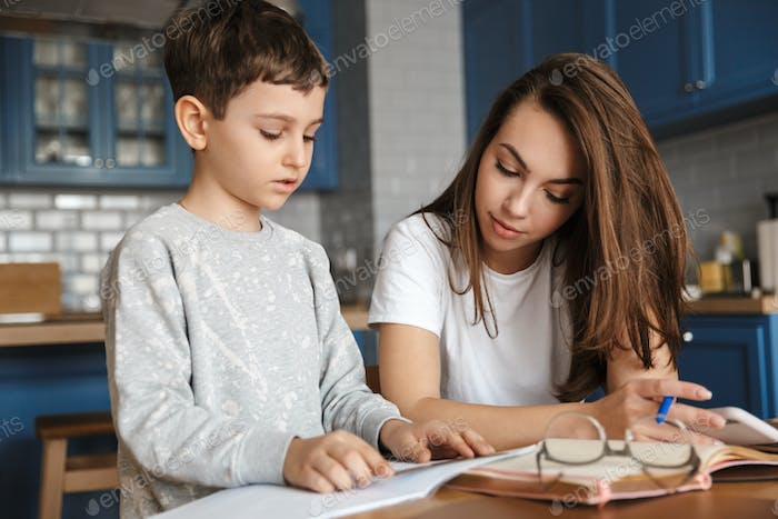 Image of nice woman and cute boy reading exercise while doing homework