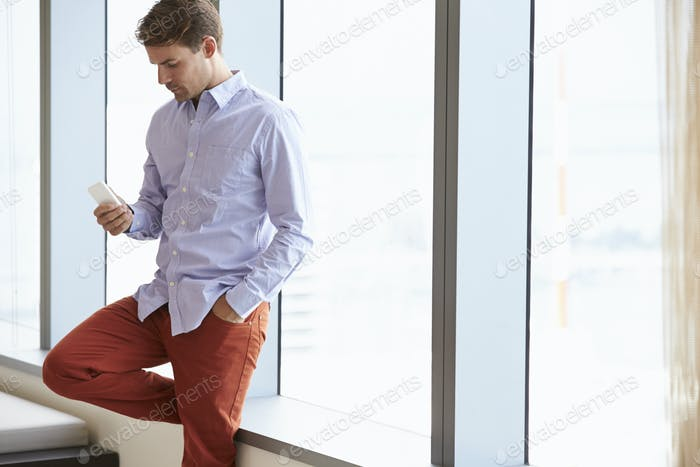 Casually Dressed Businessman Using Mobile Phone In Office