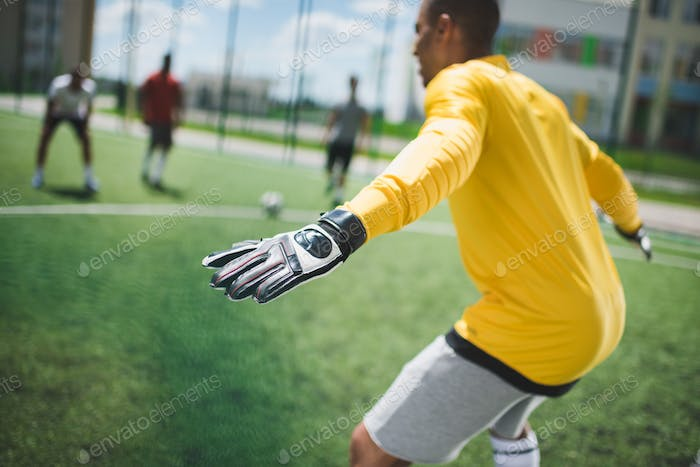 side view of african american goalkeeper standing on soccer pitch
