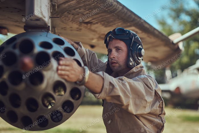 Mechaniker in Uniform und fliegender Helm reparieren alte Kriegskämpfer in einem Freilichtmuseum.