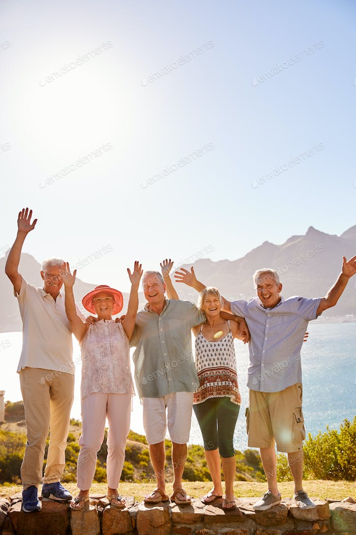 Portrait Of Senior Friends Visiting Tourist Landmark On Group Vacation With Arms Raised