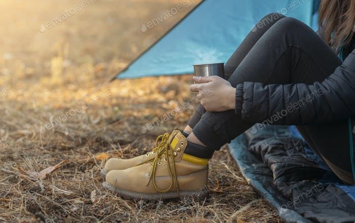 Legs in boots of woman camping in forest