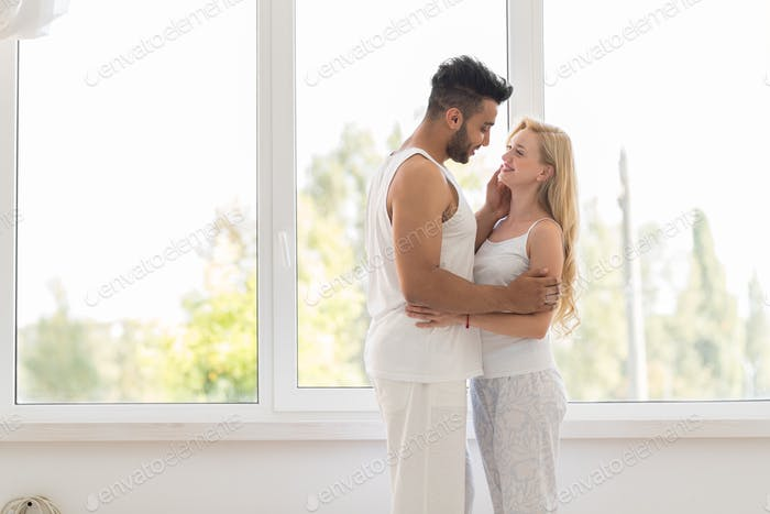 Young Beautiful Couple Stand Near Window Embrace, Happy Smile Hispanic Man And Woman