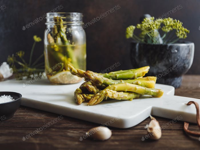 Pickled asparagus on a white marble tray. Seasonal canning vegetable recipe