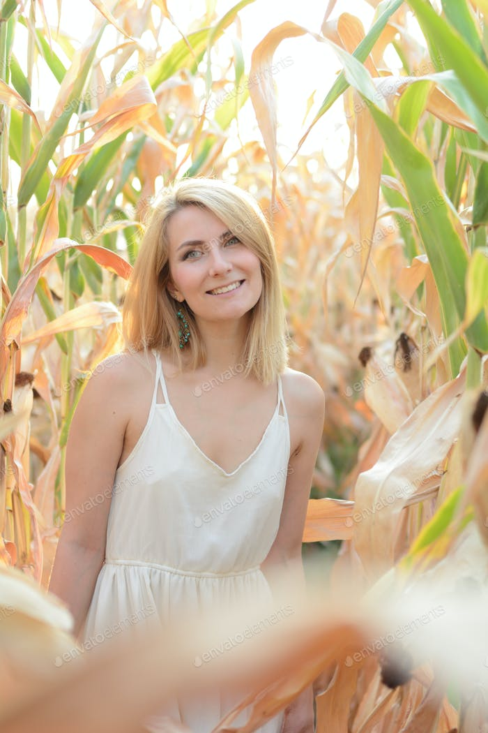 Young happy smiling caucasian woman in white dress at corn field