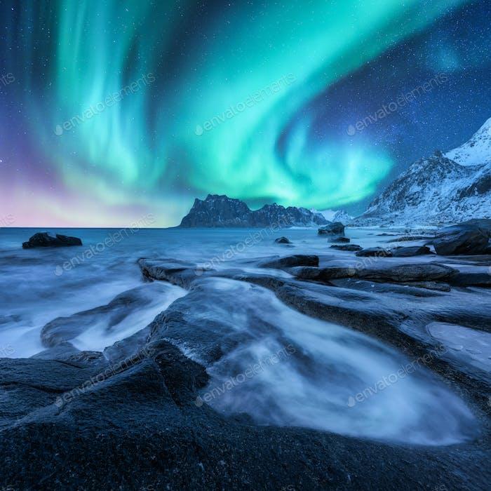 Aurora borealis, schneebedeckter Berg und Sandstrand mit Steinen