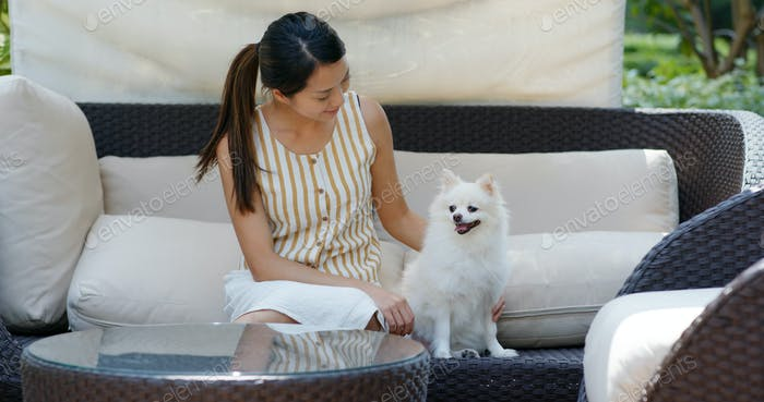 Woman play with her pomeranian dog at resort house