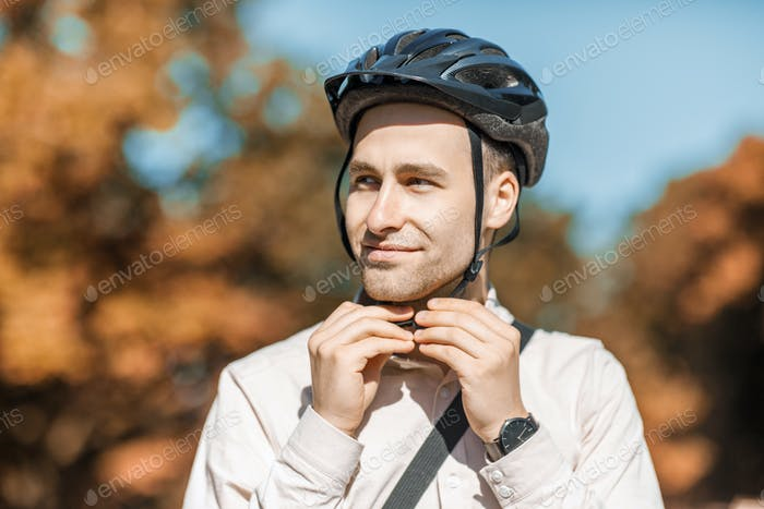 Protection while driving. Attractive young guy puts on helmet