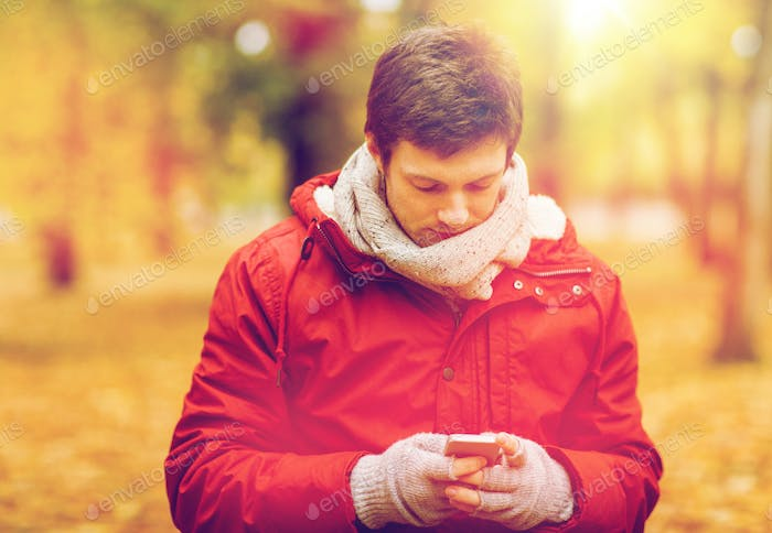 young man with smartphone walking at autumn park