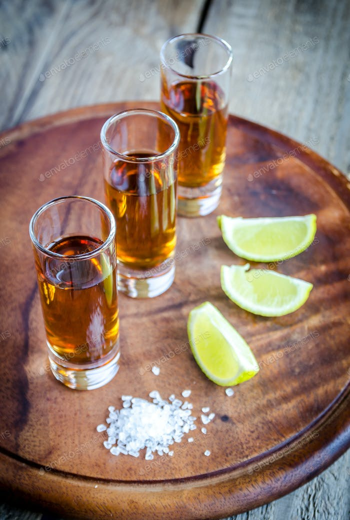 Glasses of tequila on the wooden board