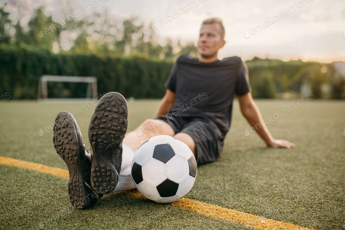 Male soccer player with ball sitting on the grass
