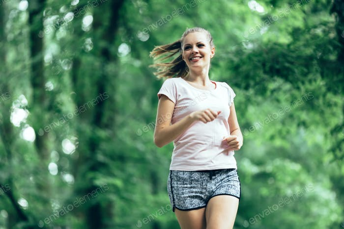 Beautiful female jogger in nature