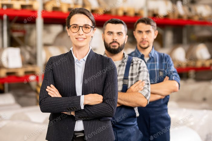 Three confident cross-armed workers of large modern chemical processing factory