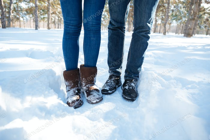 Male and female legs standing in winter park