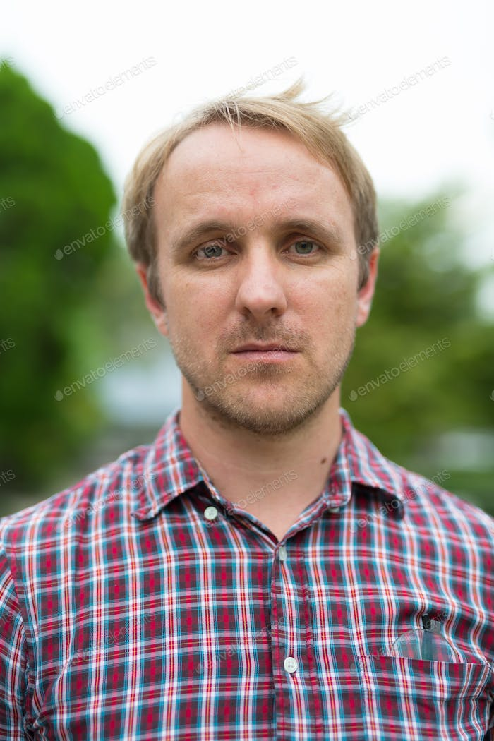 Head shot of man with blonde hair outdoors