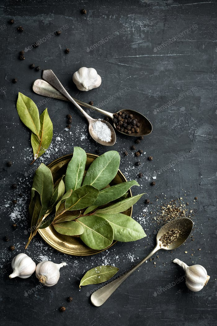 Dark culinary background with bay leaves, salt, pepper and garlic, view from above