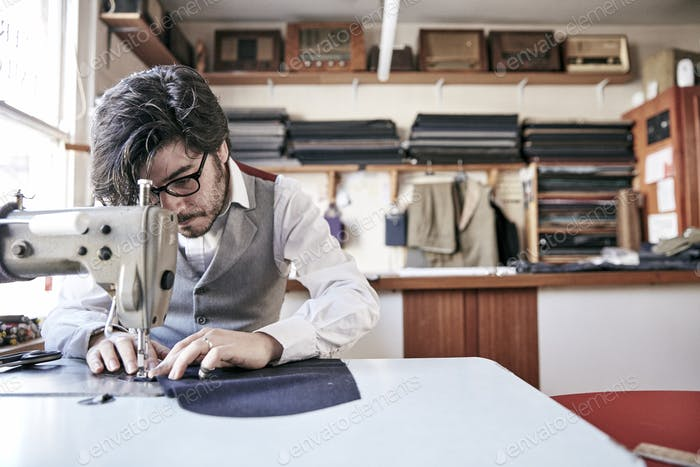 Man sewing a garment using an industrial sewing machine, at a family tailoring business workshop.