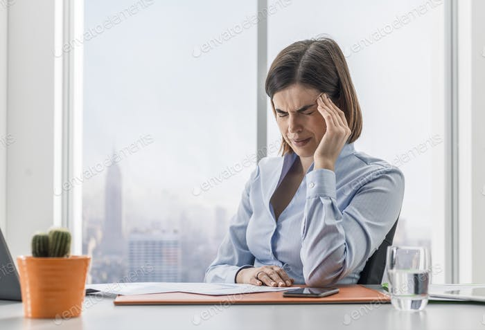Businesswoman having a bad headache in the office